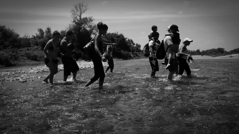 Migrantes cruzan un rio para evaadir un punto de revision migratoria